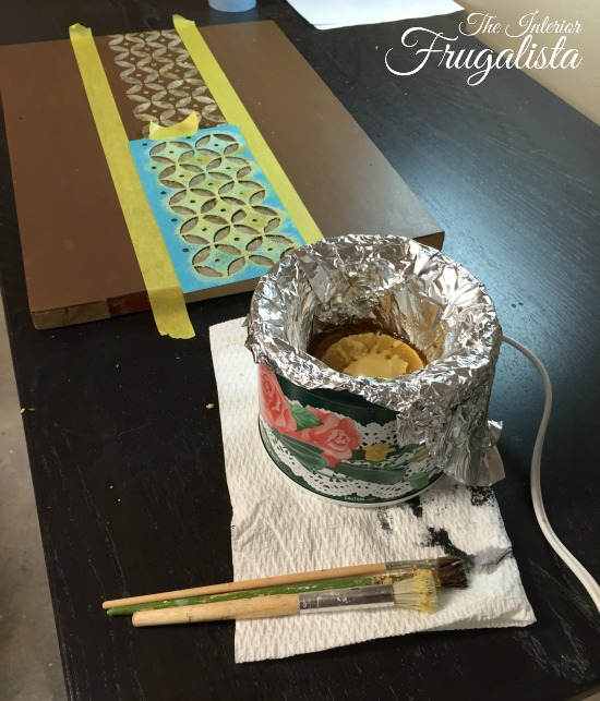 Using a stencil, a stencil brush, melted beeswax for a reverse stencil on furniture