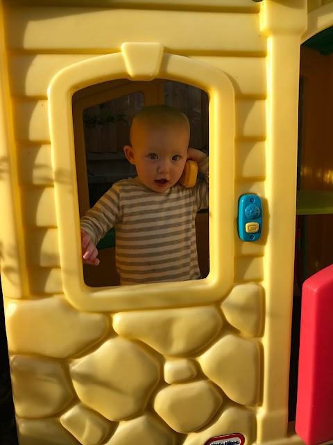 Baby in a yellow Little Tikes playhouse chatting on a bright yellow telephone