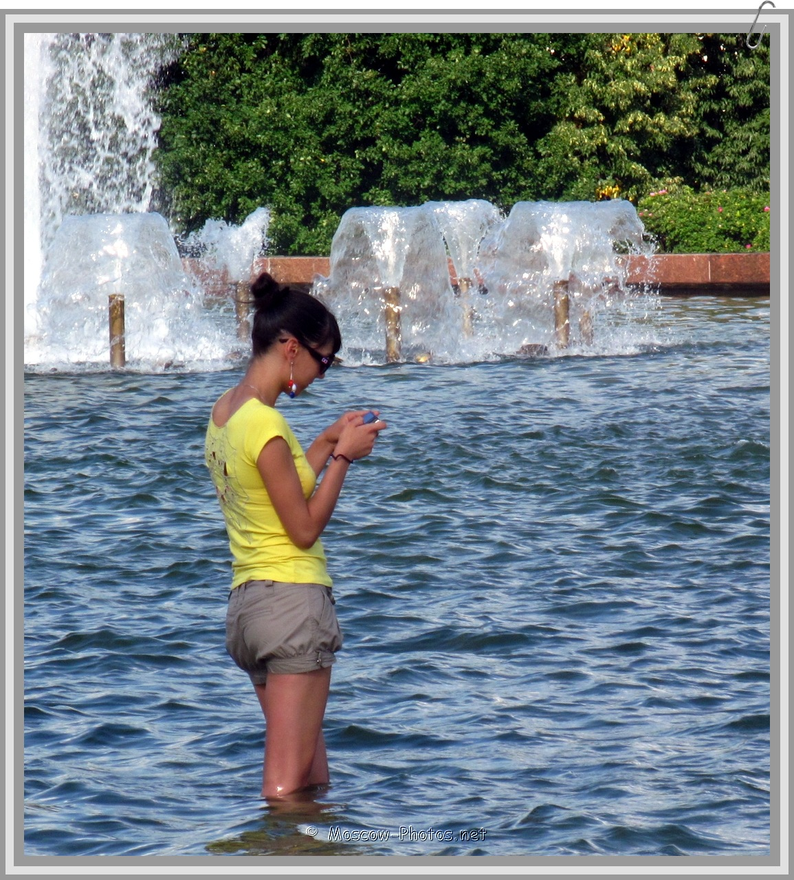 Girl with mobile phone in the fountain