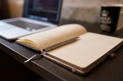 Libreta abierta en blanco y ordenador