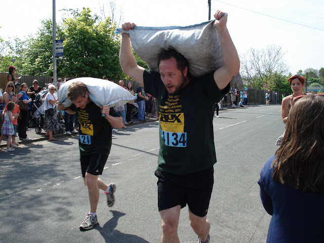 Carrying sacks of coal the competitors run up the hill