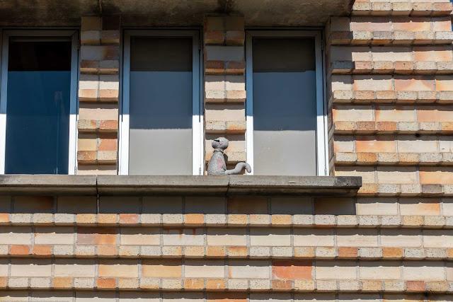 escultura de gatinho na janela de uma casa