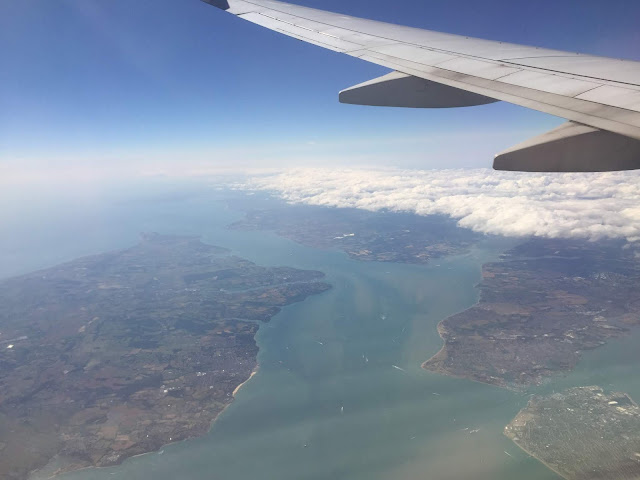 A view out of an aeroplane window showing see and islands