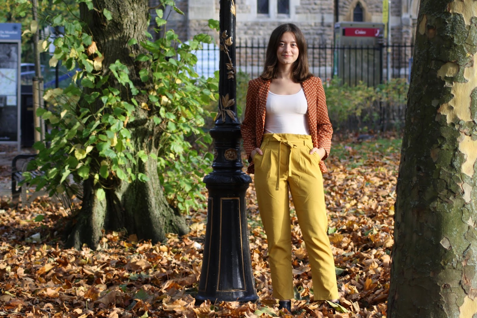 Abbey stands in a park scattered with autumn leaves, her hands in the pockets of her yellow trousers