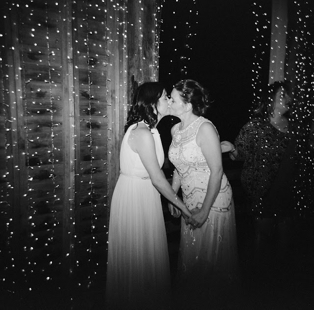 The brides kiss during the barn reception at Jonna and Heather's Inn at West Settlement Wedding by Karen Hill Photography