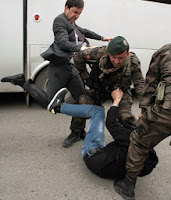 Government aide captured kicking an alleged relative of a dead Soma miner three of four times during protest