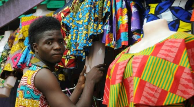 """A tailor prepares clothes to sell at an African clothes shop in Monrovia. By Zoom Dosso (AFP). Monrovia (AFP) - After almost 200 years of Western influence on their clothes, Liberians are revelling in a style revolution, designing and tailoring their own edgy creations with prints and cuts influenced by their African neighbours.  Until 2003, when a peace deal ended 14 years of devastating civil war, tens of thousands of Liberians had been living as refugees in Ivory Coast, Ghana and Guinea.  Since then, most of them have returned, bringing with them fashion influences that have translated into a vibrant homegrown industry.  Increasingly visible across the country are a wave of unique Liberian creations, which are rapidly eclipsing the once-popular combination of polo shirts, jeans and hoodies.  Back home, Liberians began asking tailors to stitch them clothes like the ones they had grown used to in Conakry or Abidjan, where people habitually wear traditional west African styles.  Insatiable demand  """"The long stay of many Liberians in other African countries during the war (was) where they saw different ways of dressing,"""" designer Agatius Coker told AFP.  These days, chic in Liberia means channelling a vibrant fierce elegance -- from edgy """"resort pants"""" slit to the thigh, to bright print shirts, or """"handkerchief"""" dresses paired with head wraps.  One of Coker's key markets is traditional African wedding celebrations, attire for which is now as sought after as the outfits for a standard European wedding.  """"The cloth is produced in African countries, we buy it and do the design here and the sewing,"""" he said."""