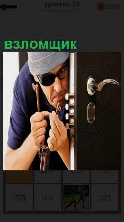 Мужчина взломщик подбирает ключ к замку на дверях