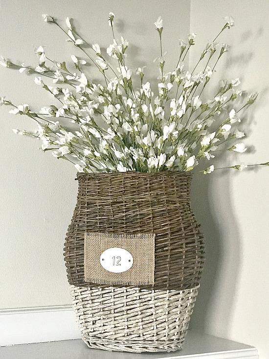 repurposed basket with tag filled with flowers
