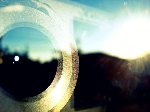 Lente de uma câmera fotográfica com uma paisagem espelhada em um vidro