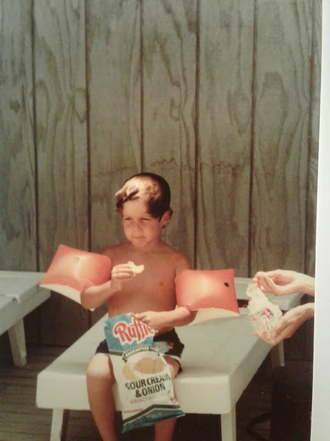 In a family photograph, Greig Roselli eats potato chips and wears floaties at the beach.
