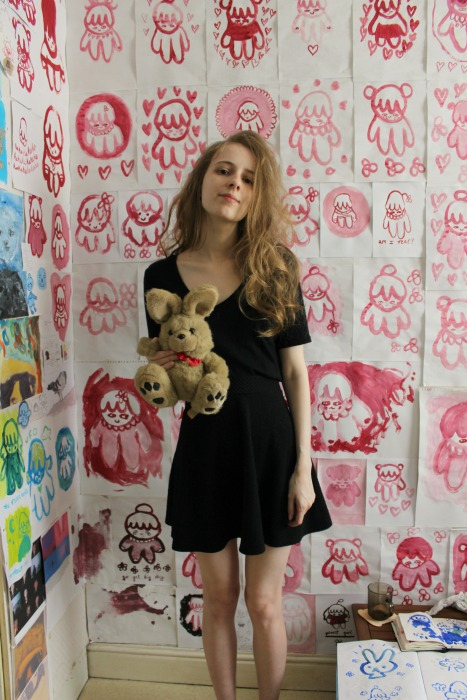Full body shot of girl standing in front of a wall of pink paintings dressed in a black t-shirt and skirt, and holding a cuddly bunny toy.