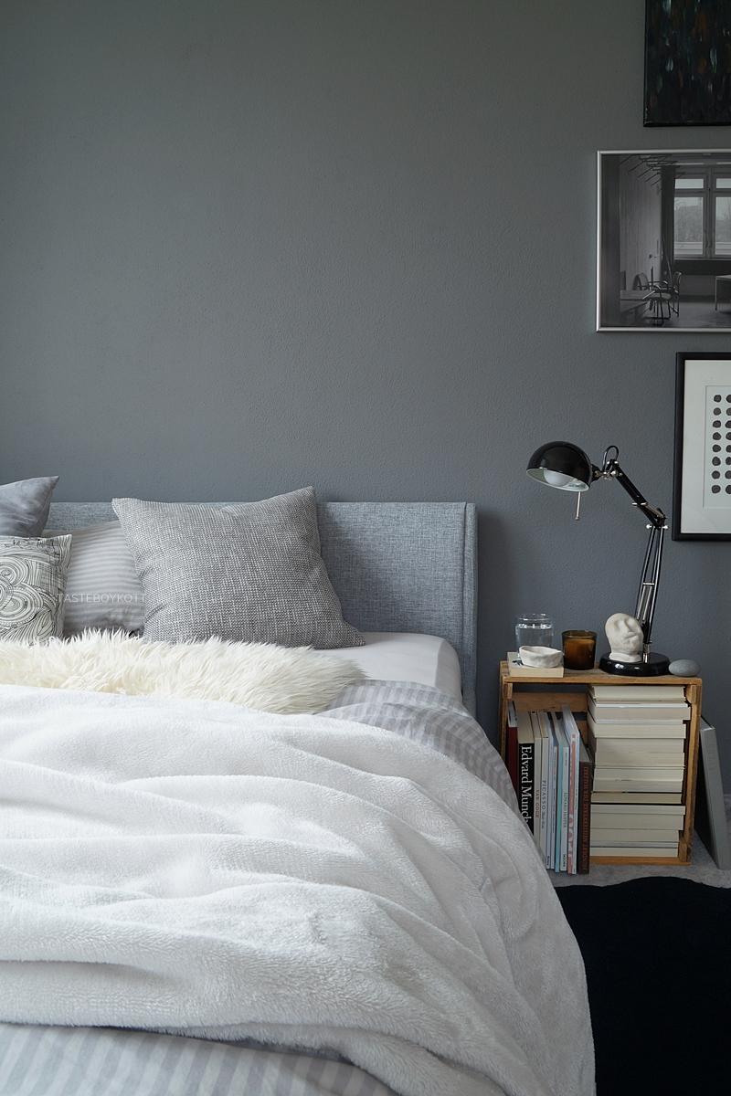 Herbstschlafzimmer in Grautönen: dunkelgraue Wand, graues Bett mit Kopfteil, Weinkiste als Nachttisch, Deko mit vielen Wohntextilien in Grau-Weiß, Ikea-Leuchte, Lieblingsstücken, Büchern, Kunst