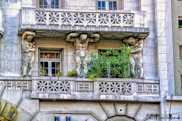 Balcón sostenido por tres columnas en forma de forzudos desnudos.