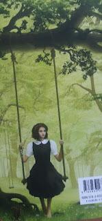 ein 13jähriges Mädchen sitzt auf einer Schaukel, die an einem Ast hängt