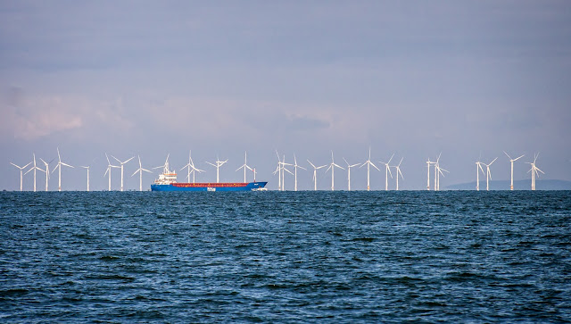 Photo of a ship passing Robin Rigg wind farm