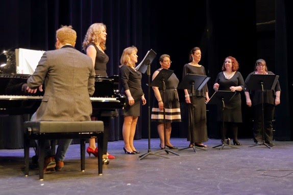 "Adult Chorus members Maria Tubelsky, Stacey Flaherty, Sonya Prear, Laurel Heske, & Angela McMillan with Director Jill Noddin (2nd from right), accompanied by Michael Sansoni, performing Billy Joel's ""And So It Goes"" at the recent Music & Art Appreciation Night sponsored by The Center for Adult Education & Community Learning."