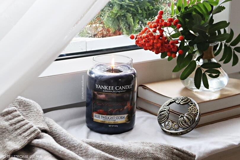 duża świeca yankee candle pali się na parapecie obok ciepłego swetra i gałązki jarzębiny