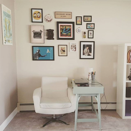 image of my home workspace, showing my desk, a white chair, and various art pieces on the wall above