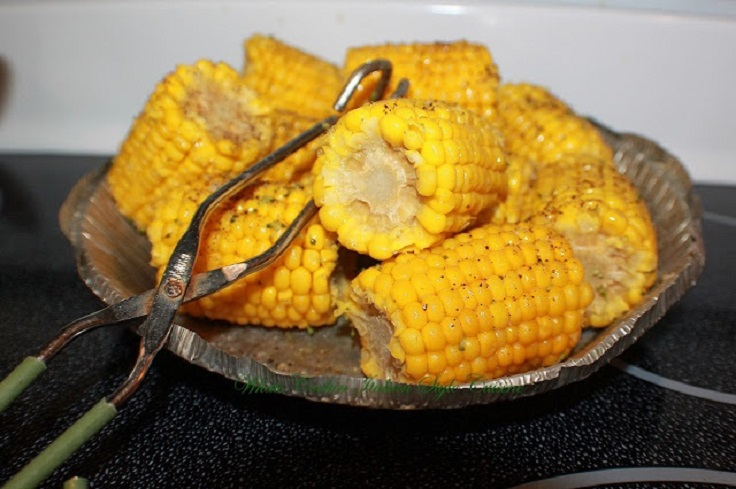 Boiled Corn on the Cob in a foil dish with tongs to grab them with