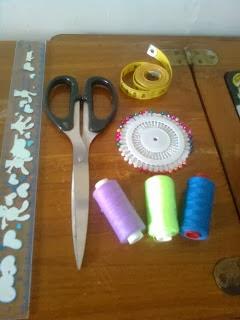penggaris, gunting, meteran, benang, jarum pentul, jarum jahit untuk membuat kerajinan kain perca