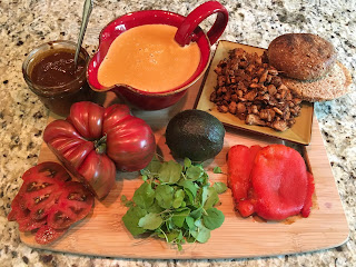 Photo of ingredients for Cemita Torta, including (clockwise from top left) adobo, Mexican queso, Mexican jackfruit, Ezekiel bun, roasted red bell pepper, avocado, papalo, and heirloom tomato on a bamboo cutting board. https://trimazing.com/