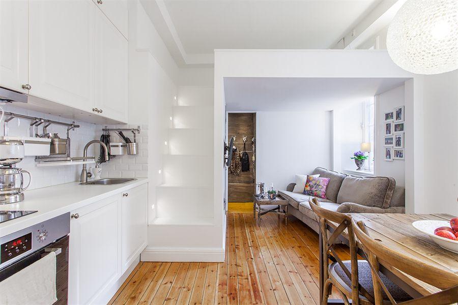 piso con cama en altillo y cocina blanca