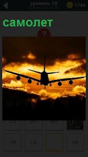 Идет на посадку в вечернее время самолет. Закат  и только силуэт с крыльями видно
