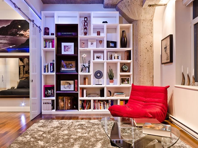 Picture of bookshelf and red sofa with glass table