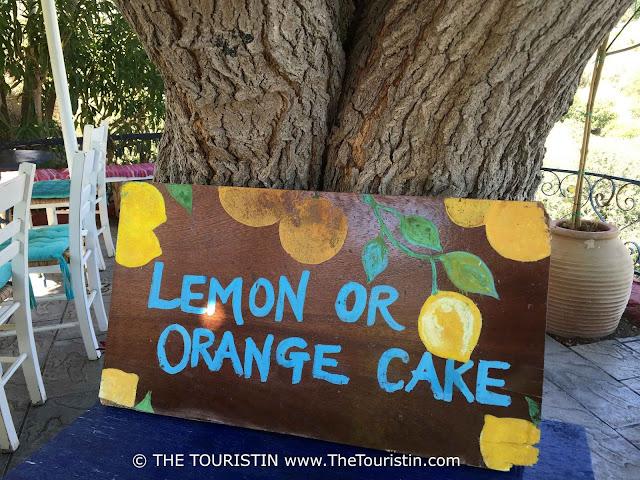 Wooden sign on a blue table under a tree, promoting Lemon or Orange Cake