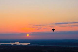 Αερόστατο πετάει πάνω από κοιλάδα στο ηλιοβασίλεμα. Ακολουθεί το κείμενο: Τώρα ανοιξιάτικο καθώς ανάβρυσες απ' την καρδιά μου, πέτα, τραγούδι μου, στο φως, πέτα τριγύρω και μακριά μου.    Ως τη χαρά της εξοχής την ηχηρή χαρά σου φέρε, κι ένα τριαντάφυλλο αν ιδείς, πες του από μέρος μου το χαίρε.
