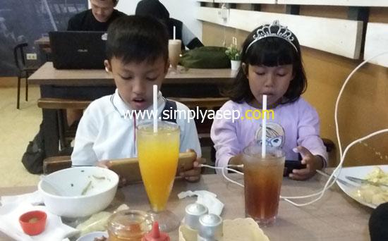 SANTAI : Anak anak saya juga asyik dengan menu pilihannya masing masing. Mas Abbie (8) memilih Bubur Singkawang sedangkan adiknya Tazkia (7) dengan Nasi Gorengnya. Foto Asep Haryono