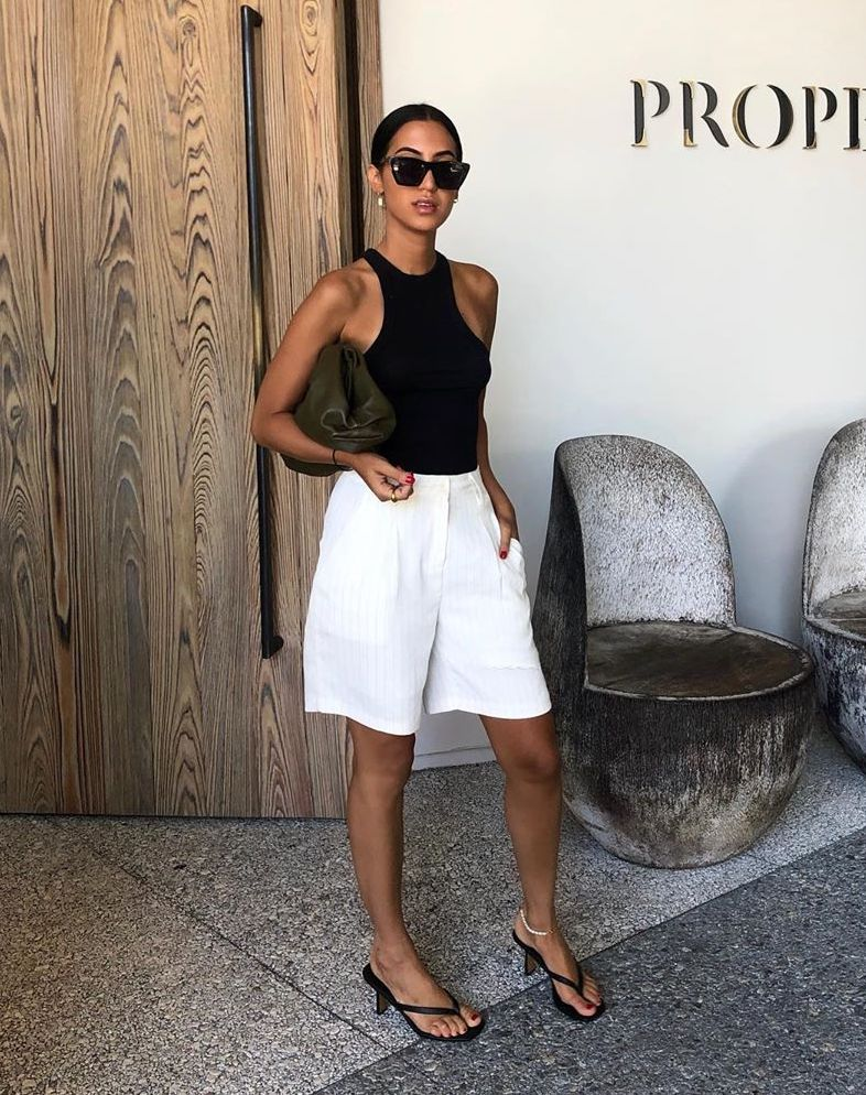 How to Wear White Shorts for Summer — Tania Sarin in black sunglasses, a racerback tank top or bodysuit, a pouch clutch, long white shorts, and heeled flip-flop sandals.