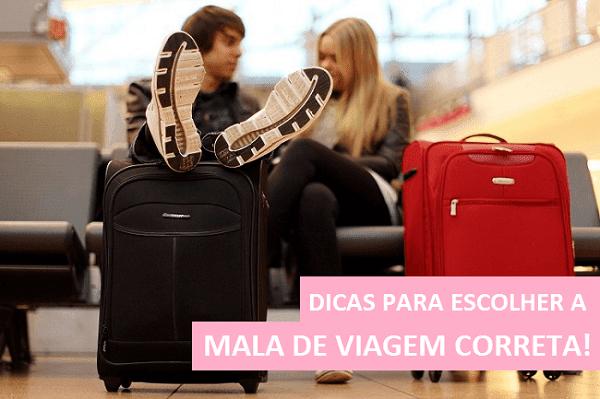 Casal sentado em aeroporto com malas de viagem pequenas posicionadas a frente. Malas nas cores preta e vermelha.