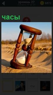 В песке на дороге стоят большие деревянные песочные часы, которые показывают определенное время