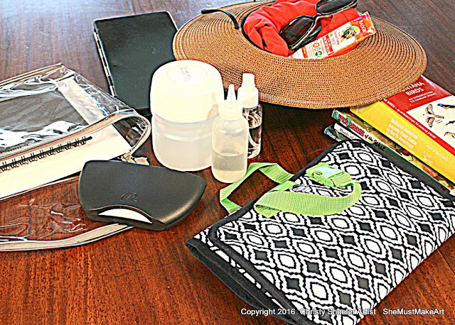 Laying out the basic art supplies for a watercolor artist's kit.  Watercolor paint palettes, zipper bag, sun care supplies.