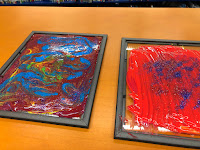 two black frames with colorful paint in swirl patterns