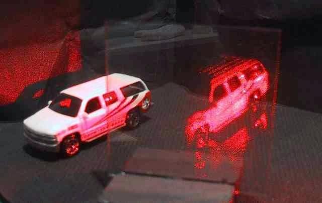 Fotografia de um carrinho de brinquedo de um lado, e a projeção em laser deste carrinho em um acrílico logo ao lado dele.
