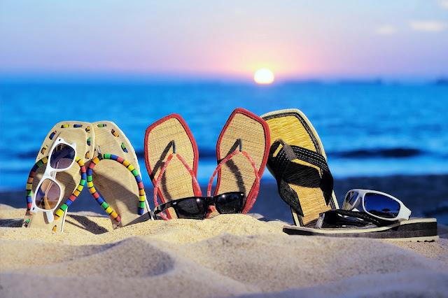 Strand, zee, ondergaande zon en slippers