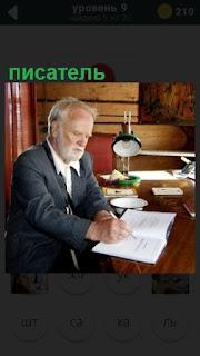 мужчина писатель сидит за столом и пишет