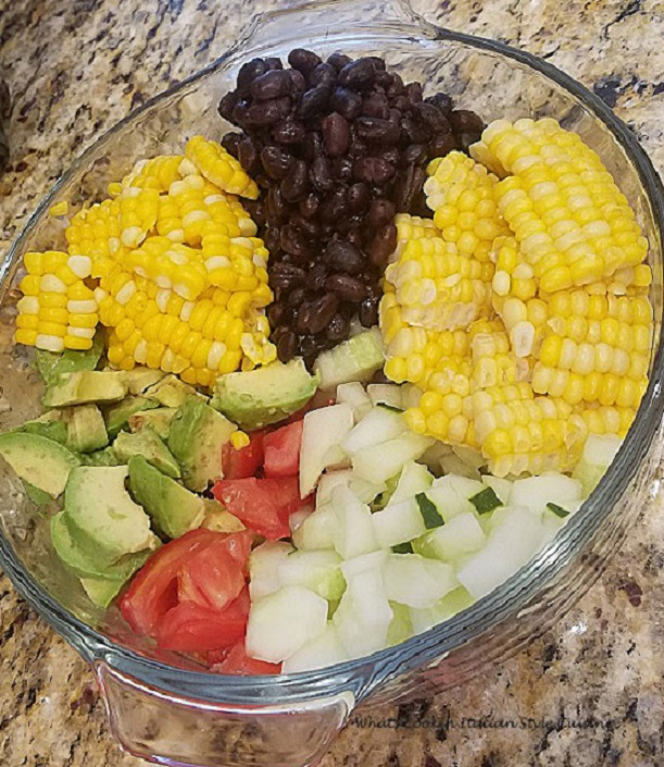 this is a bowl of Tex Mex style salad with black beans, chopped tomato, cubed cucumbers, shucked corn off the cob, avocado with a lime dressing