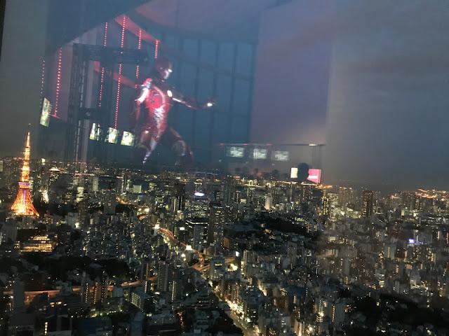 マーベル展で展示されている巨大アイアンマンと展望台からの夜景の写真です。