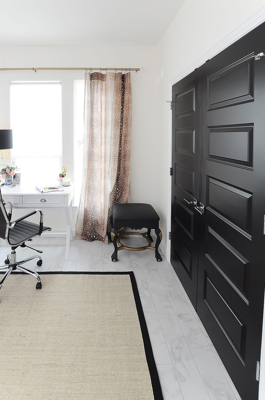Black closet doors look chic when paired with antelope curtains in a white and gold home office makeover.