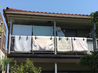 Two top and two bottom futons clipped firmly to the balcony on the second floor of a house