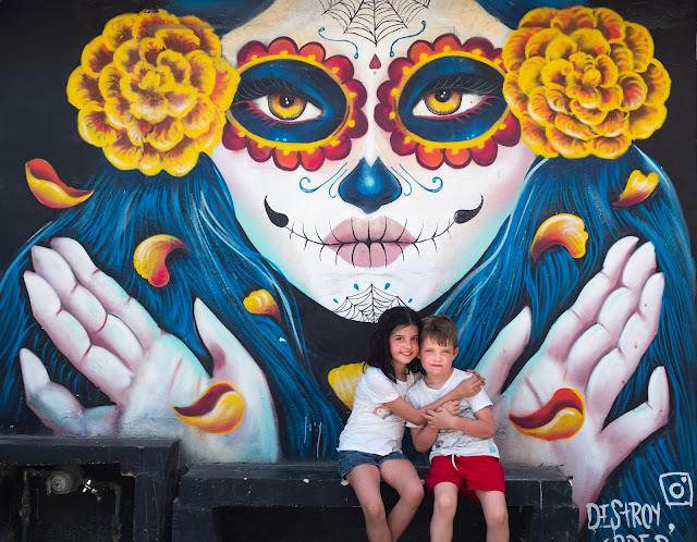 Mural de Catrina con niños sentados delante