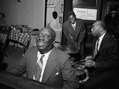 James P Johnson, smiling, playing the piano with other musicians in the background