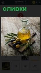 На разделочной доске стоит графин с оливковым маслом и сами оливки, из которых оно сделано