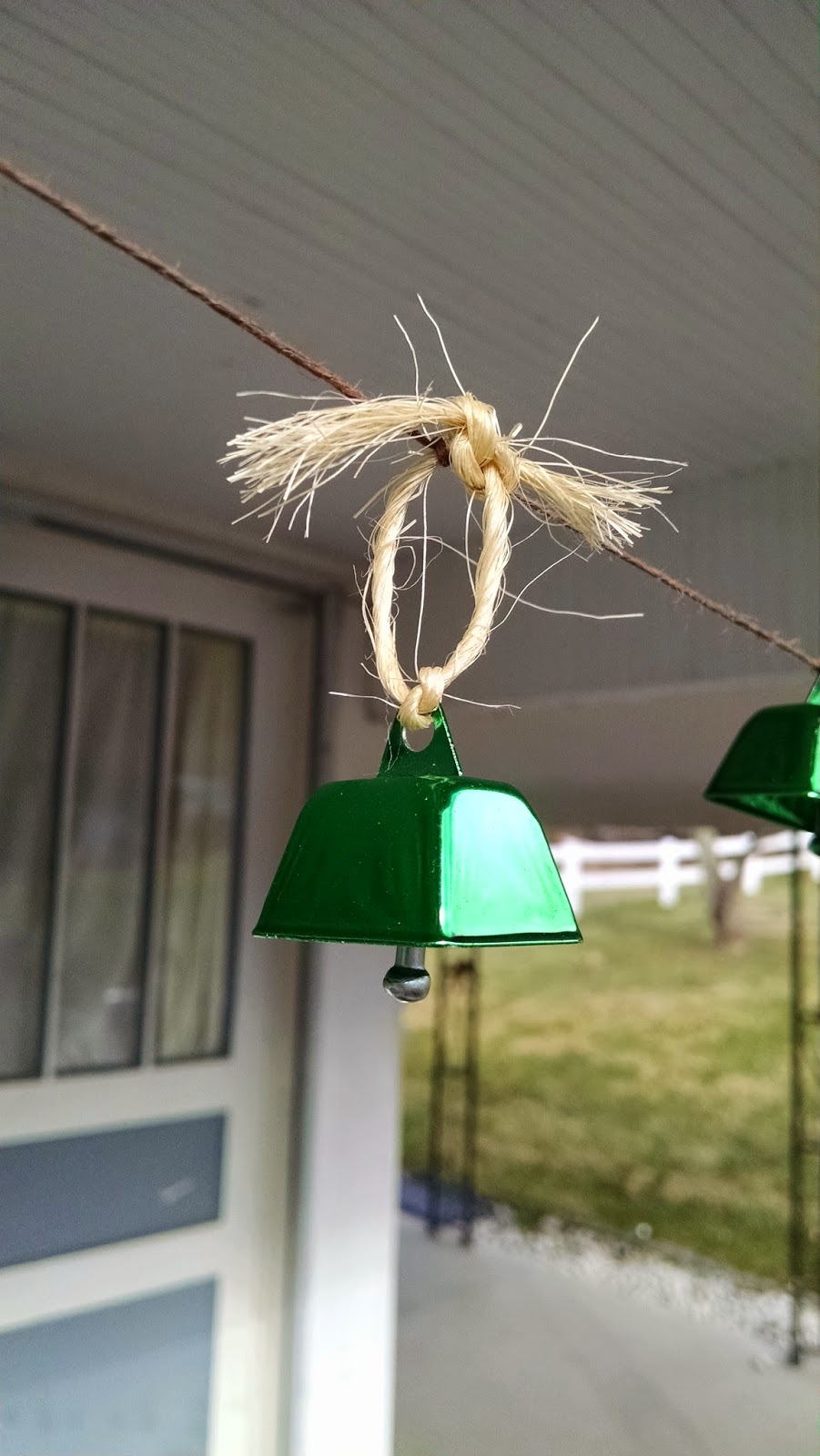 tiny green hanging cowbell with twine