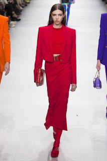 A woman with medium brown shoulder length hair wearing a bright red long sleeve top that has a gold bow at the bottom of it with bright red long pants with red heels on a white rectangular catwalk on a bright background.
