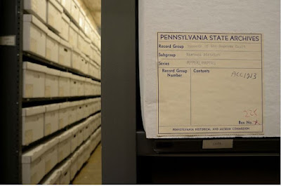 Left third of image shows rows of white archival boxes on metal shelves. Right two-thirds is close-up view of one box with a label detailing the contents. Heading on label is Pennsylvania State Archives
